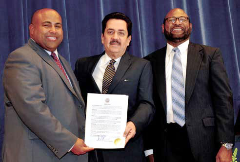 The Ninth International Book Fair was dedicated in honor of Tony Raful and Gabriel Garcia Marques, who received a posthumous tribute. Tony Raful, center, receiving a Resolution from Lawrence Mayor Daniel Rivera while Father Joel Almono, president of the Book Fair smiles happily. Tony Raful, centro, recibiendo una Resolución de manos de Daniel Rivera, Alcalde de Lawrence mientras que el Padre Joel Almonó, Presidente de la Feria Internacional del Libro sonríe satisfecho.